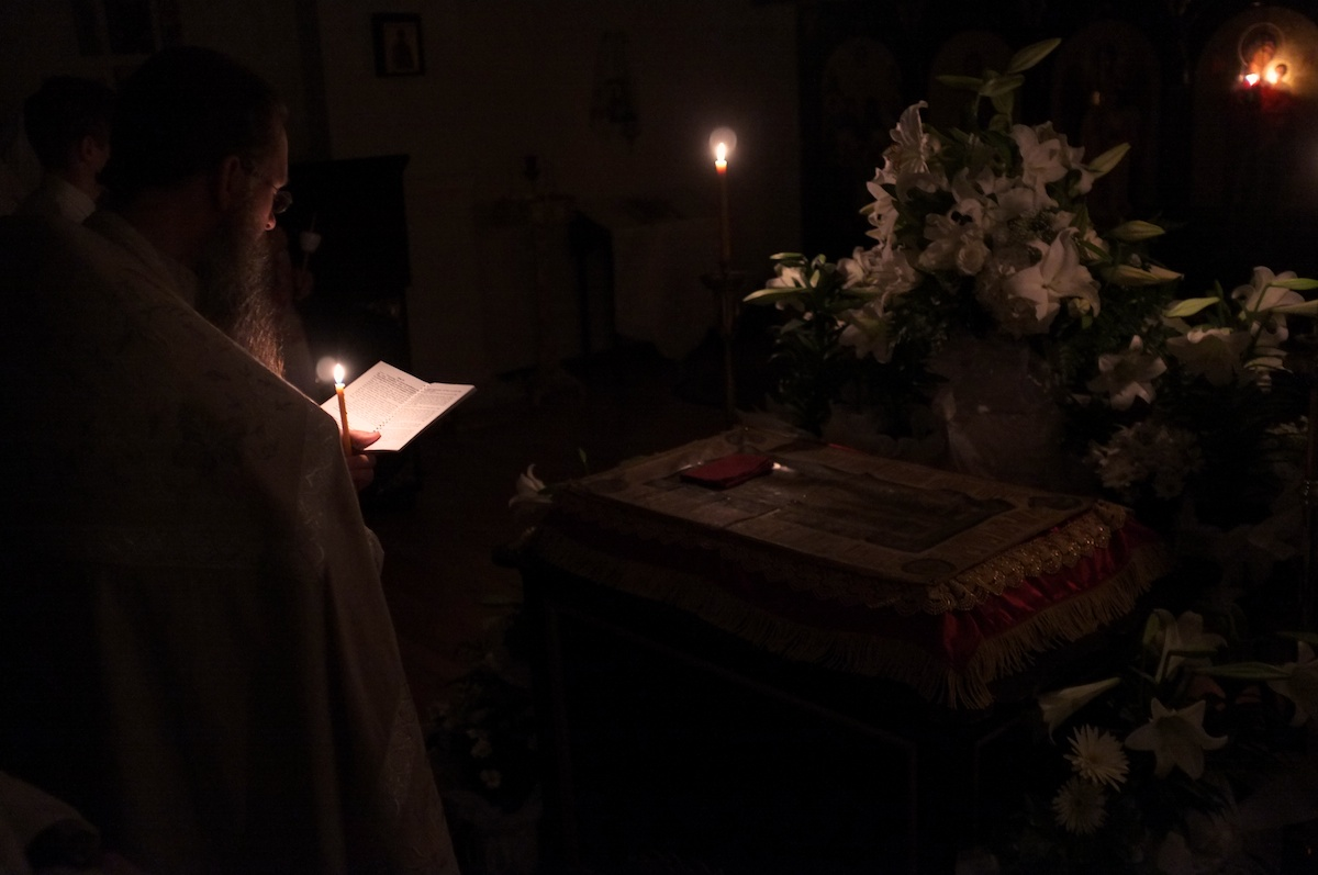 Orthodox priest reading at the tomb.