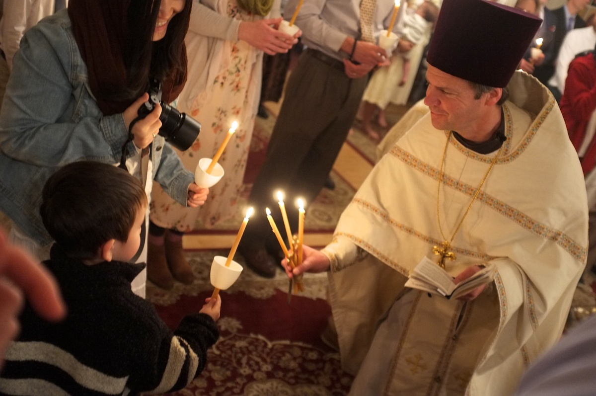 priest lighting candle from a child