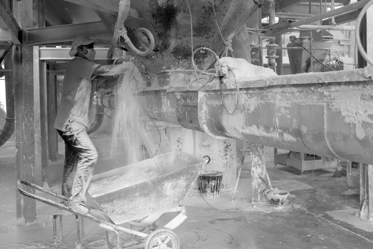 Worker cleans out a port for extracting kaolin powder.